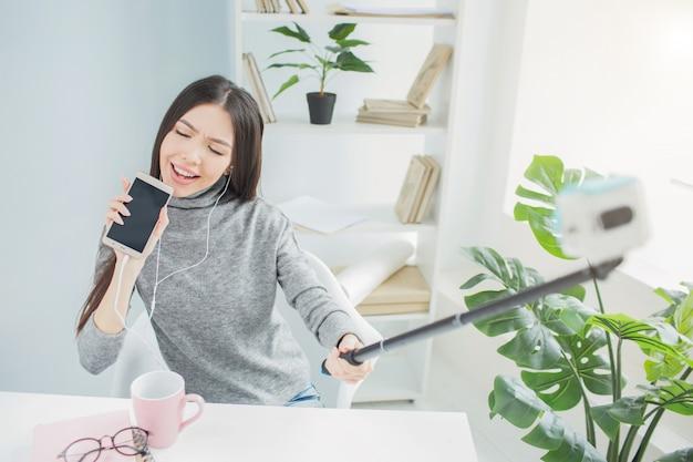 Grappige vrouw doet alsof ze een lied zingt en een telefoon gebruikt in plaats van een microfoon