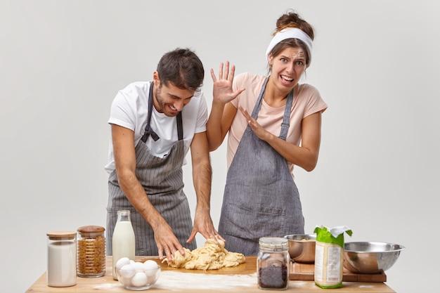 Grappige vrouw en man maken deeg voor taart, hebben vrolijke gezichten, gekleed in schorten, doen culinaire ervaring op, hebben wat problemen, voegen ingrediënt niet volgens recept toe. kooktijd, bakken concept