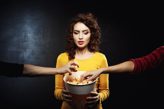 Grappige vrouw houdt er niet van om snacks te delen met vrienden in de bioscoop