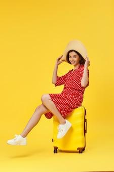 Grappige vrouw in rode jurk met koffer gaan reizen op gele achtergrond.
