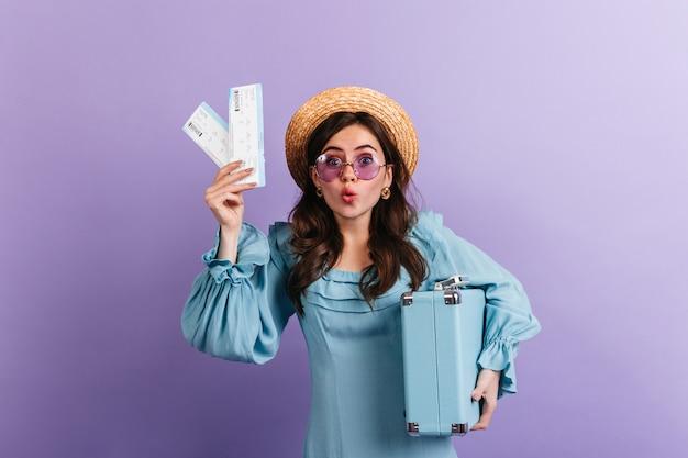 Grappige vrouw in schipper en lila bril staart in verbazing, toont haar vliegtickets en blauwe retro koffer.
