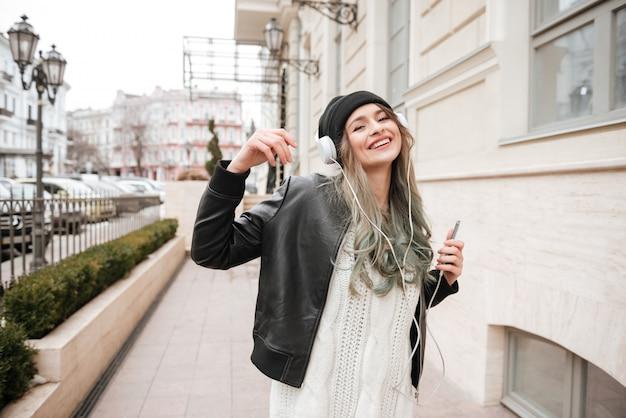 Grappige vrouw in warme kleren luisteren muziek op straat