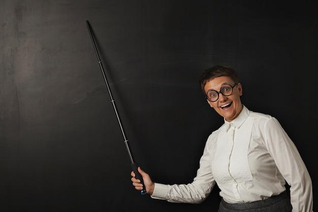 Grappige vrouw leraar met lachend stom gezicht in ronde glazen toont gelukkig iets met haar aanwijzer op krijtbord op zwart