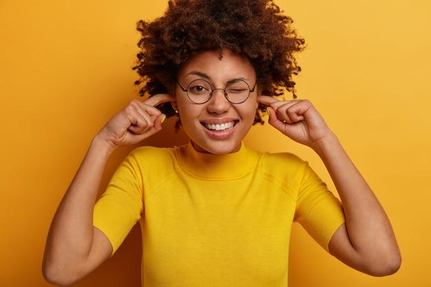 Grappige vrouw met donkere huid steekt vingers in de oren, kan zich niet concentreren vanwege lawaai op een drukke plaats, knipoogt naar de ogen en toont witte tanden, draagt een bril en een t-shirt, geïsoleerd op een gele muur