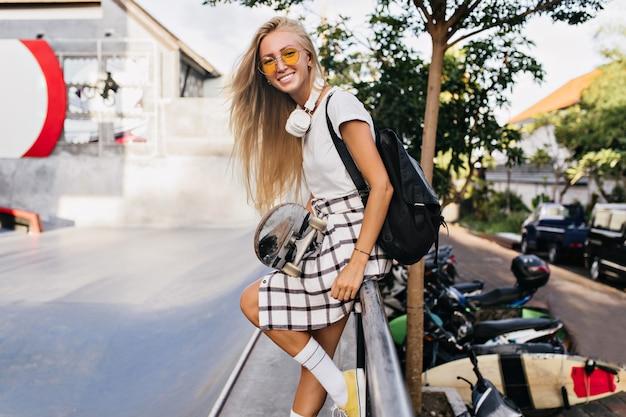Grappige vrouw met een gebruinde huid poseren met skateboard en lachen. outdoor portret van sensuele blonde vrouw in gele zonnebril genieten van de zomer in het weekend.