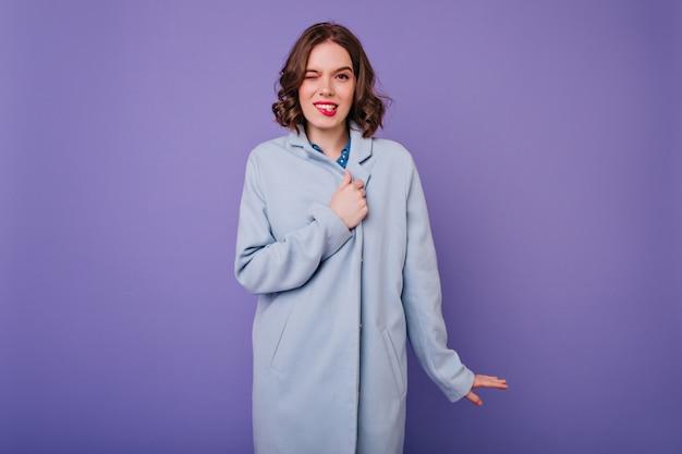 Grappige vrouw met golvend haar staande in blauwe jas. prachtig kaukasisch meisje met lichte make-up gezichten op paarse muur maken.