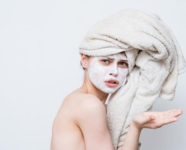 Grappige vrouw met handdoek op hoofd blote schouders wit masker op gezicht.