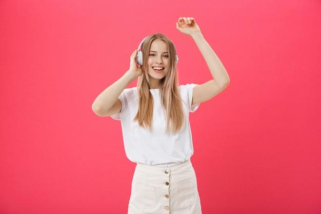 Grappige vrouw met hoofdtelefoons die zingen en aan de muziek dansen luisteren