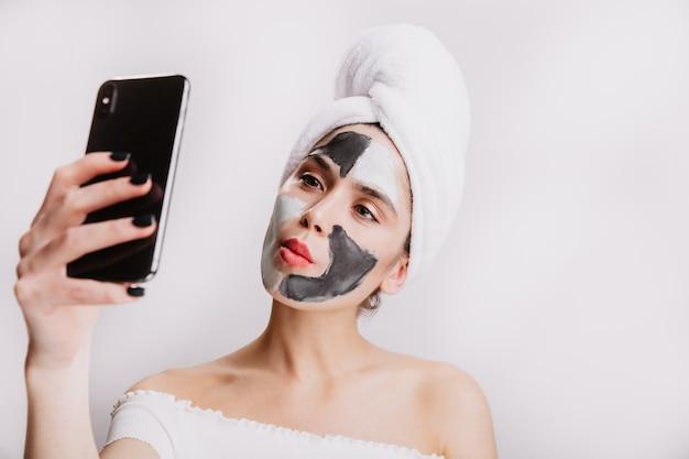 Grappige vrouw met kleimasker voor gezichtsverzorging en in handdoek op haar hoofd maakt selfie op witte muur.