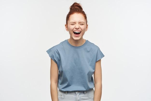 Grappige vrouw, mooi meisje met gemberhaar verzameld in een broodje. blauw t-shirt en spijkerbroek dragen. lachend met gesloten ogen, hoor hilarische grappen. emotie concept. tribune geïsoleerd over witte muur