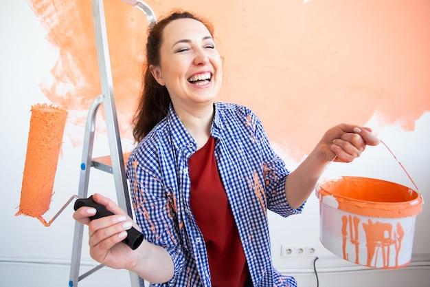 Grappige vrouw schilderij muur in haar nieuwe appartement