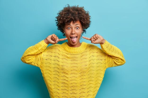 Grappige vrouw steekt tong uit wijst wijsvinger naar mond heeft uitdrukking verbaasd draagt gele gebreide trui geïsoleerd over blauwe muur