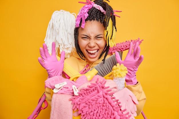 Grappige vrouw van gemengd ras houdt handen omhoog en draagt roze beschermende rubberen handschoenen