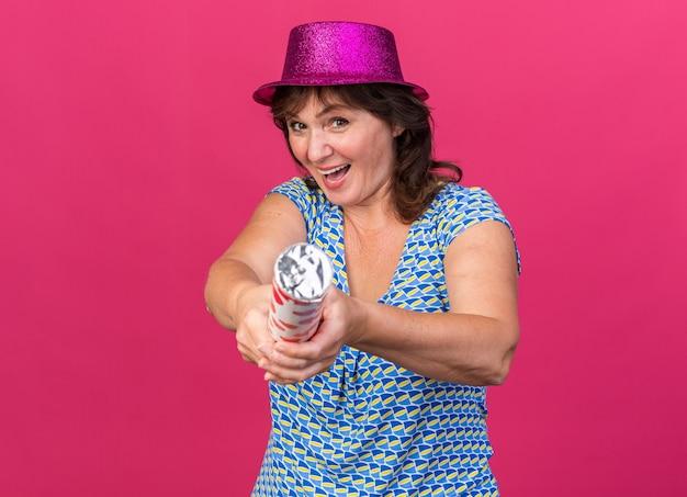 Grappige vrouw van middelbare leeftijd in feestmuts met petard blij en opgewonden holding