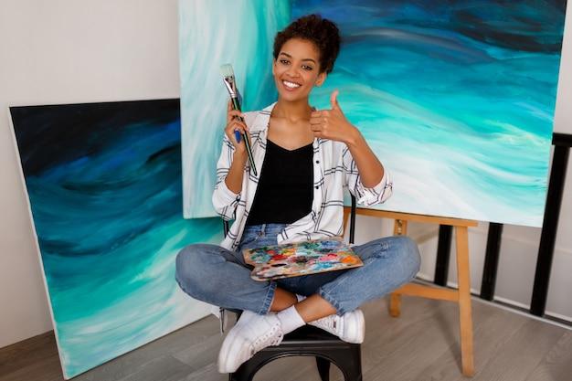 Grappige vrouwelijke kunstenaar zit met verbazingwekkende abstracte zee acryl handgetekende kunstwerken. penselen en palet vasthouden