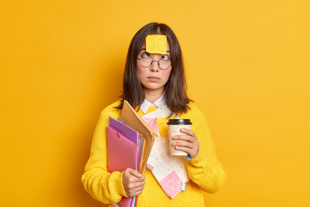 Grappige vrouwelijke nerdy student kruist ogen heeft plaknotitie geplakt op voorhoofd koffiepauze tijdens de voorbereiding op examen veel werk te doen houdt mappen en papieren.