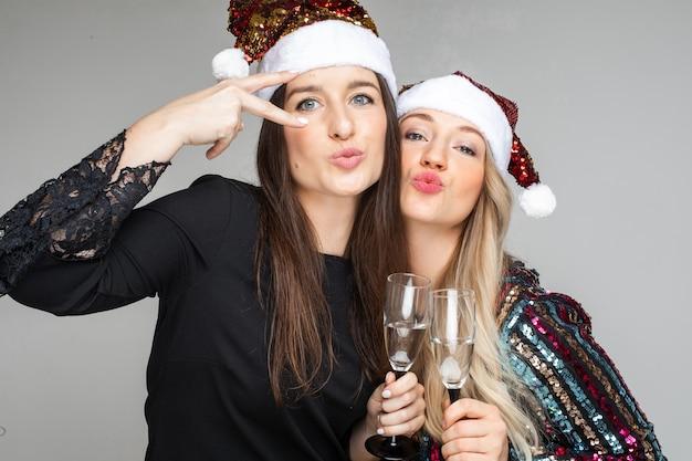 Grappige vrouwen in jurken en kerstmutsen drinken champagne en poseren voor de camera