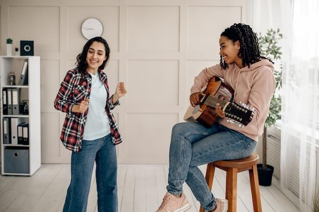 Grappige vrouwen spelen gitaar en dansen thuis