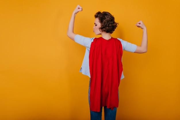 Grappige wonderwoman die haar spieren bekijkt