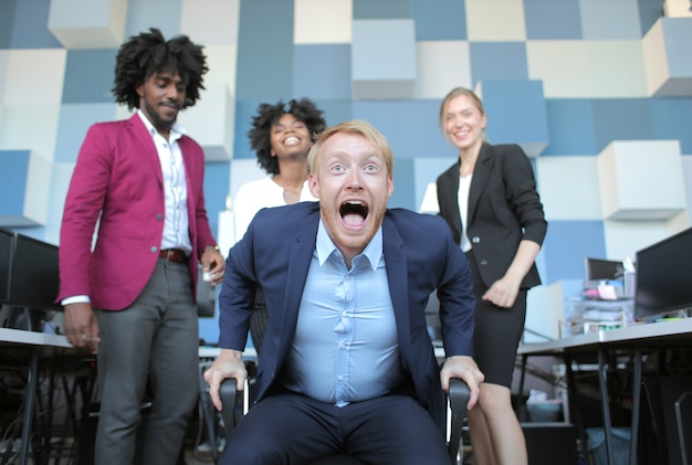 Grappige zakelijke teamleider die gelukkig schreeuwt na een productieve ontmoeting met zijn multi-etnische collega's