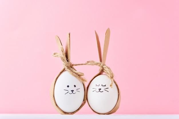 Grappige zelfgemaakte eieren met gezichten op een roze oppervlak. pasen of gelukkig paarconcept