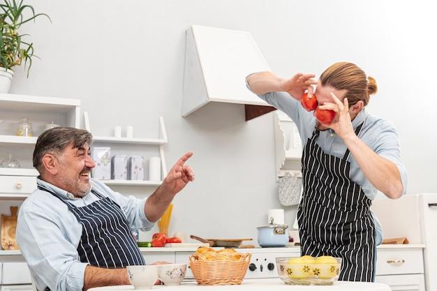 Grappige zoon die tomatenogen maakt