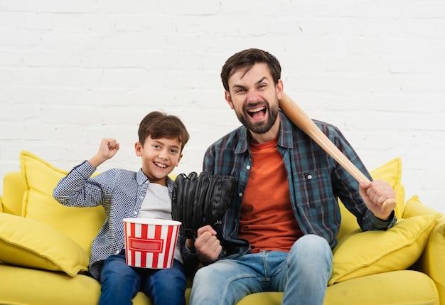 Grappige zoon en vader die een honkbalknuppel houden
