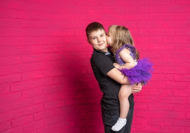 Grappige zusje kussen knuffelen haar knappe oudere broer tiener op roze achtergrond.