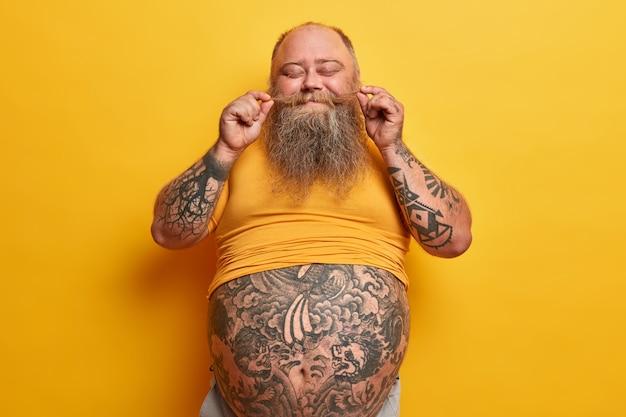 Grappige zwaarlijvige man dwarrelt snor, voelt zich trots op een dikke baard, poseert met een getatoeëerde dikke buik, gekleed in een casual ondermaats t-shirt, heeft plezier, geeft niet om gewicht, sluit ogen van plezier