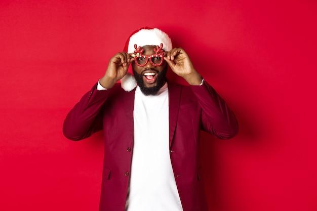 Grappige zwarte man die nieuwjaar viert, een feestbril en een kerstmuts draagt, plezier heeft op rode achtergrond