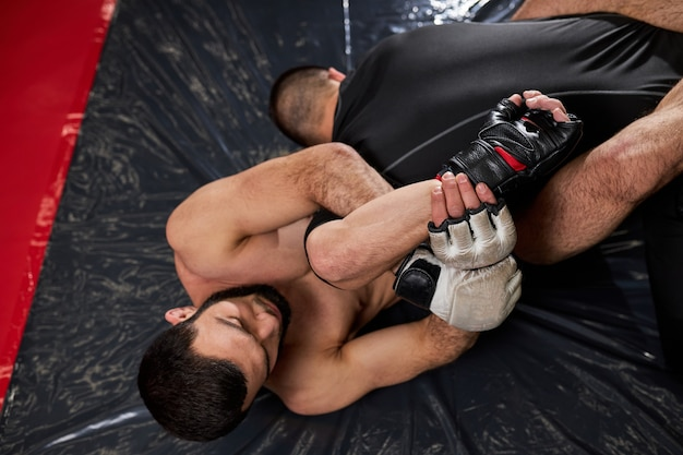 Grappler probeert tegenstander te stikken in grondgevecht, training in de sportschool... twee atletische mannen die zich bezighouden met mma, boksen, vechten zonder regels. bovenaanzicht