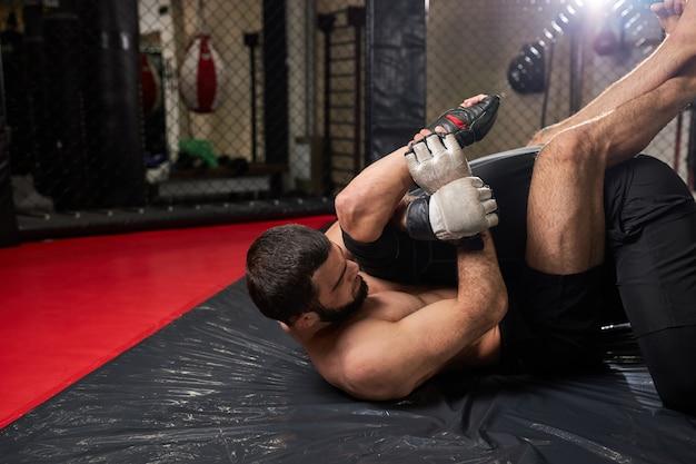 Grappler probeert tegenstander te stikken in grondgevecht, training in sportschool... twee atletische mannen bezig met mma, boksen, vechten zonder regels