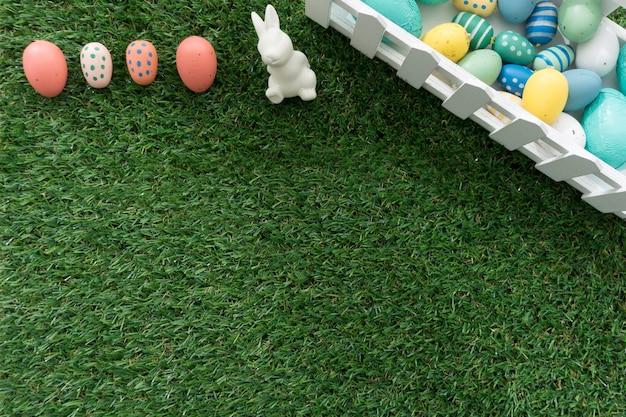 Gras achtergrond met gekleurde eieren en paashaas