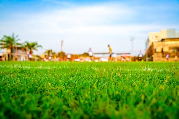 Gras op het voetbalveld met onscherpte speler spelen voetbal achtergrond.