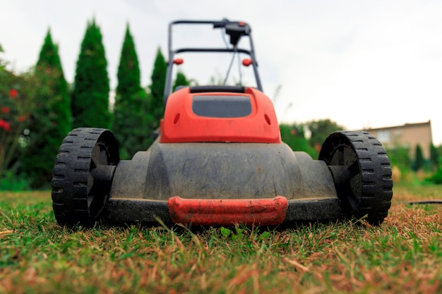 Grasmaaimachine die groen gras in binnenplaats snijdt.