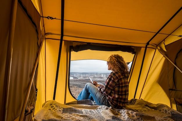 Gratis alternatieve vakantievrouw in een tent die naar het panorama buiten kijkt en technologie met internet verbonden mobiele telefoon gebruikt om verbonden te blijven met de rest van de beschaafde wereld