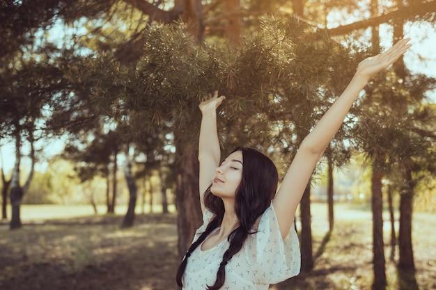 Gratis gelukkige vrouw in het bos genieten van de natuur natuurlijke schoonheid meisje buiten in vrijheid genieten concept