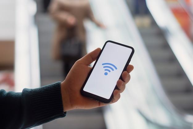 Gratis internet in de supermarkt. man houdt een mockup vast van een smartphone met een pictogram op een wit scherm tegen de achtergrond van de roltrap en mensen in het winkelcentrum.