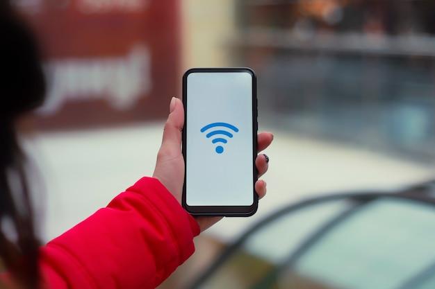 Gratis internetten in de supermarkt. vrouw houdt een mockup van een smartphone met een pictogram op een wit scherm tegen de achtergrond van de roltrap in het winkelcentrum.
