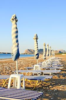 Gratis ligstoelen en parasol op het strand in de zomer