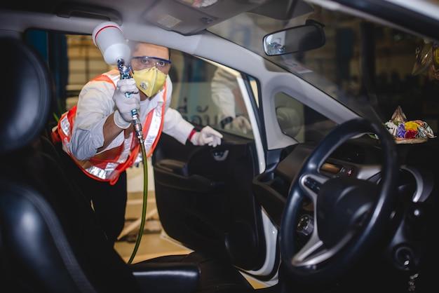 Gratis service voor injectie van het covid-19-virus in de auto. foto van een monteur die een beschermend masker draagt en het covid-19-desinfectiemiddel in de auto spuit.