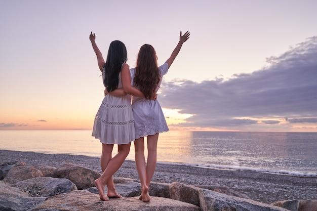 Gratis zorgeloze gelukkige dochter en moeder in korte witte jurken staat samen op een steen met open armen aan de kust bij zonsondergang in de zomer
