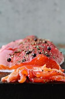 Gravlax, scandinavische met biet gezouten gekruide zalm op het bord, bovenaanzicht, gezouten rode vis