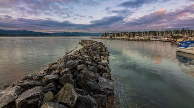 Gray rocks near watermassa onder blauwe hemel