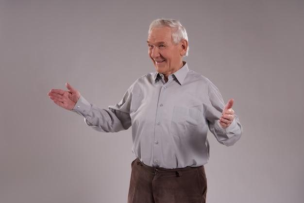 Grayhaired oude man verwelkomt met open armen tegen op grijs.
