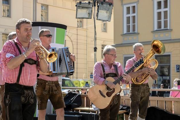 Graz / oostenrijk - september 2019: jaarlijks herfstfestival van de volkscultuur van stiermarken (aufsteirern). groep mannen in heldere traditionele jurken volksmuziek spelen op een stadsplein.