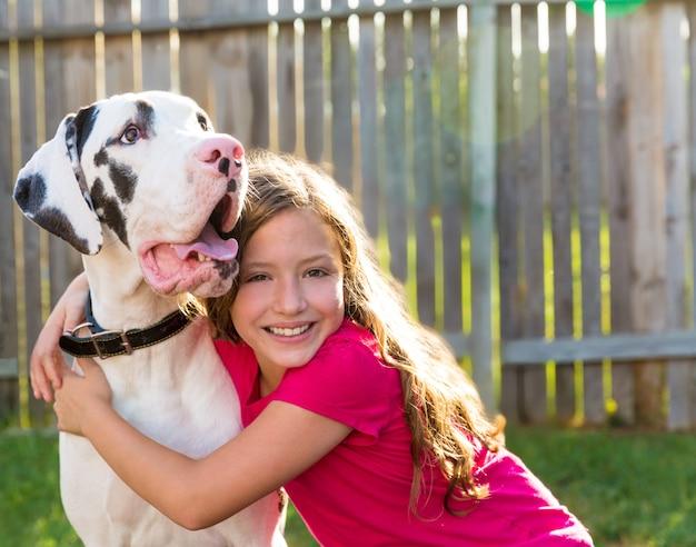 Great dane en kind meisje knuffel buiten spelen