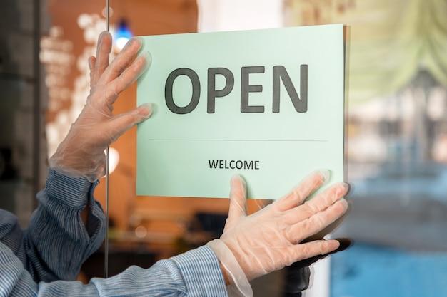 Green sign open welkom covid 19 lockdown heropenen als nieuw normaal. heropeningsteken open op voordeuringang. vrouw in beschermende medische handschoenen hangt open bord aan de deur van de winkel, café, kantoor.