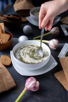 Greens dovga witte lichte soep met verschillende kruiden op grijs