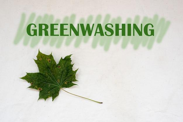 Greenwashing concept droog esdoornblad en tekst met groene markeringsstrepen